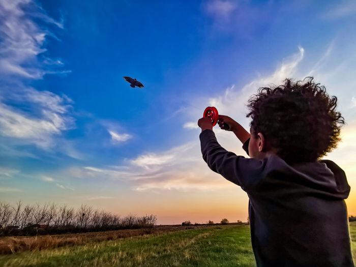 Rear view of cute boy flying kite in sky