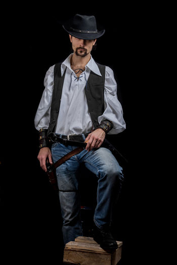 Handsome young man. This is an American cowboy. A vow to a white shirt, brown waistcoat and blue jeans. Black shoes on the feet. Carries a shtyapa, on a belt two pistols. The hair is of medium length; on the face is a beard and mustache. Authentic photo. Culture of America. Cowboy Wild West America American Gun National Authentic Moments Lifestyles Lifestyle One Person Candid Authentic Hat Clothing Black Background Front View Holding Casual Clothing Full Length Men Standing Three Quarter Length Males  Young Adult Young Men