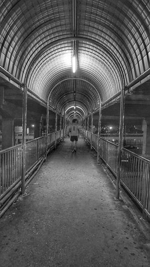 Full length rear view of man walking on illuminated walkway