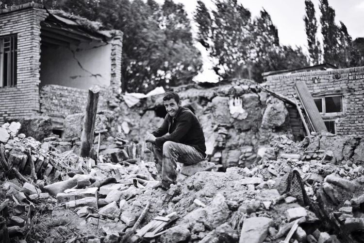 Man sitting on rock amidst demolished building