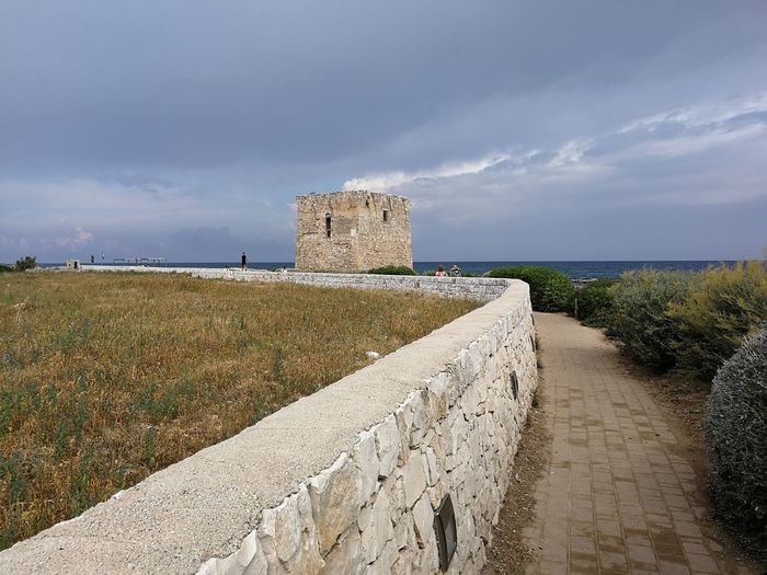 Sky History The Past Architecture Cloud - Sky Wall Ancient Fort Grass Nature Castle Day The Way Forward Plant Travel Destinations Old Ruin Stone Wall Outdoors Ruined Ancient Civilization Footpath Polignano A Mare Torre Adriatic Sea Sentiero