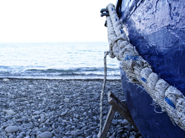 Blue Blue Sky Blue Wave Boat Clear Sky Day Geology Horizon Over Water Nature Non-urban Scene Outdoors Rock Rope Scenics Sea Solitude Stone - Object Stone Material Tranquil Scene Tranquility Water