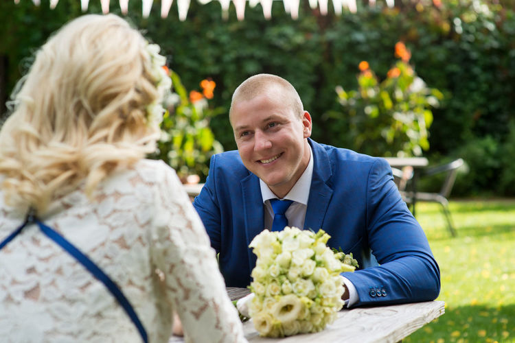 Smiling groom looking at bride sitting at table in park