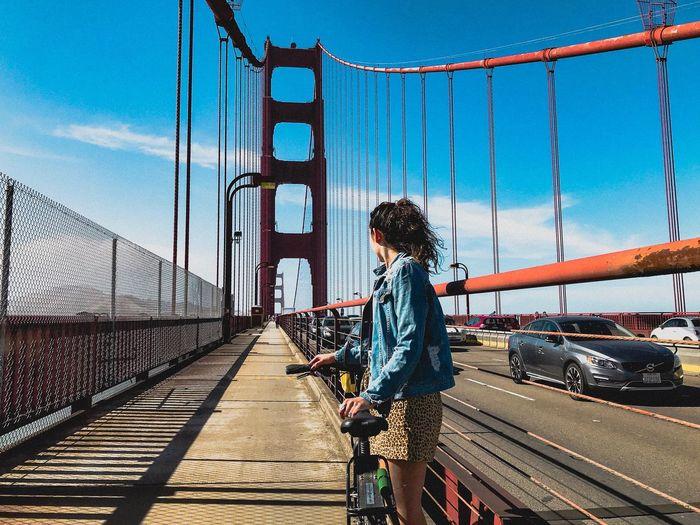 Side view of woman standing on footbridge against blue sky