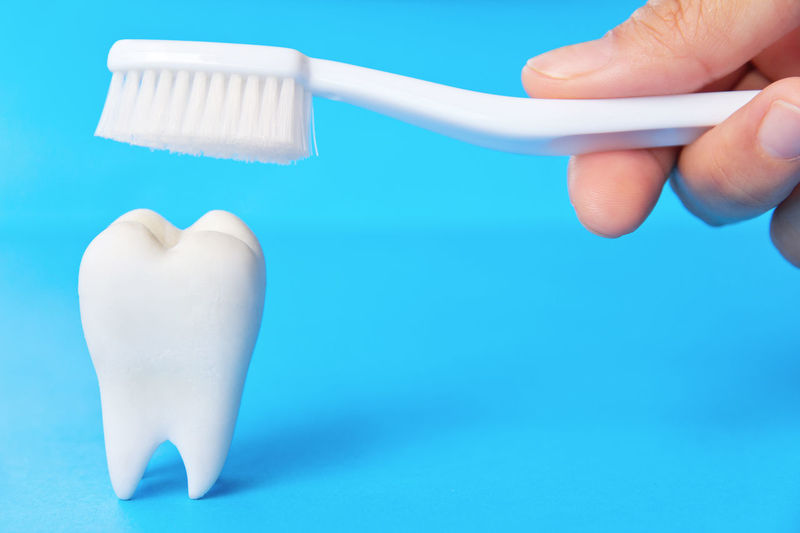 Cropped hand holding toothbrush over dentures against blue background