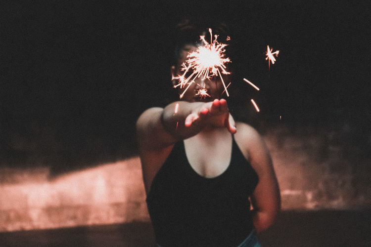 Midsection of woman with fire crackers at night