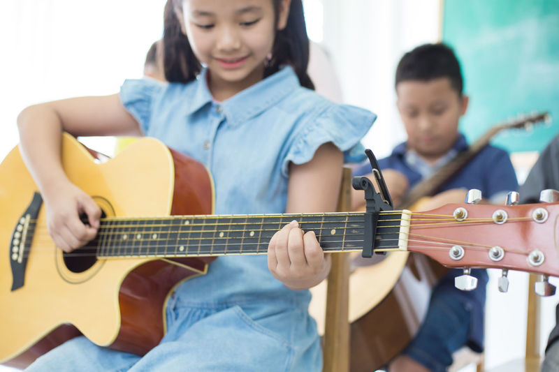 Asian little girl playing guitar Acoustic Guitar Arts Culture And Entertainment Casual Clothing Focus On Foreground Front View Guitar Holding Leisure Activity Lifestyles Music Musical Equipment Musical Instrument Musician Playing Plucking An Instrument Real People Sitting Skill  String Instrument Two People Women