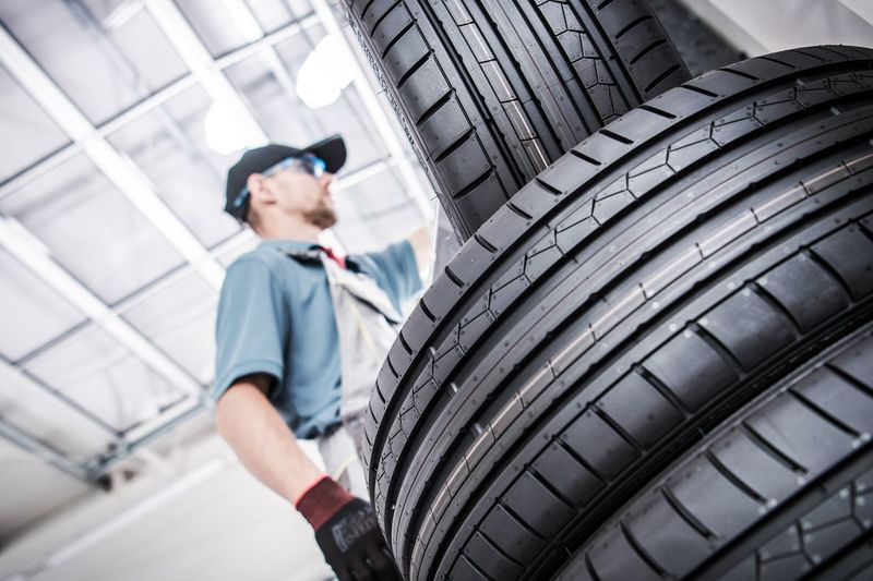 Low angle view of mechanic by tires