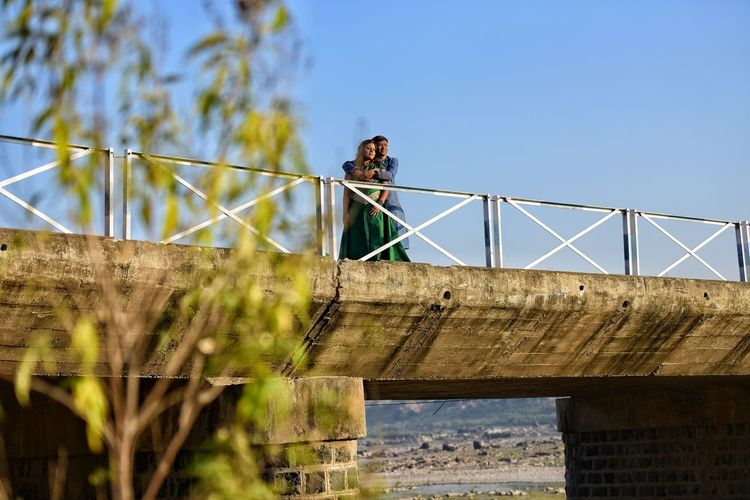 Low Angle View Of Young Couple On Bridge Against Sky