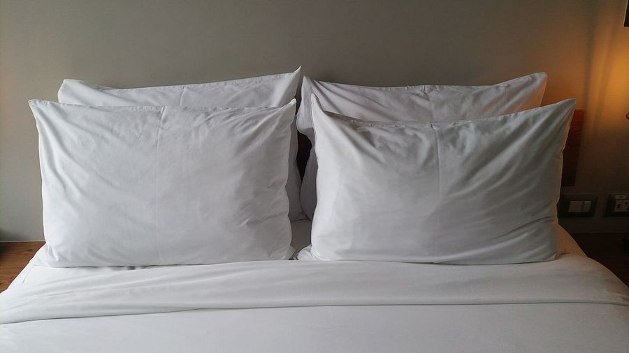 High angle view of pillows with sheet arranged on bed at home