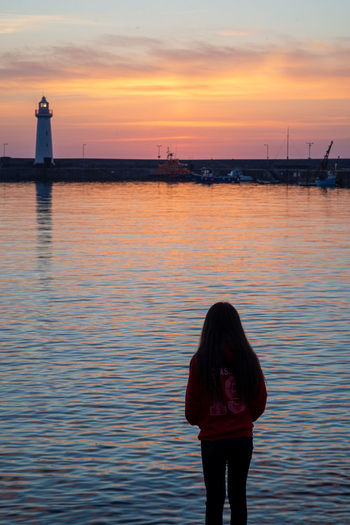 Rear view of woman standing by sea against sky during sunset