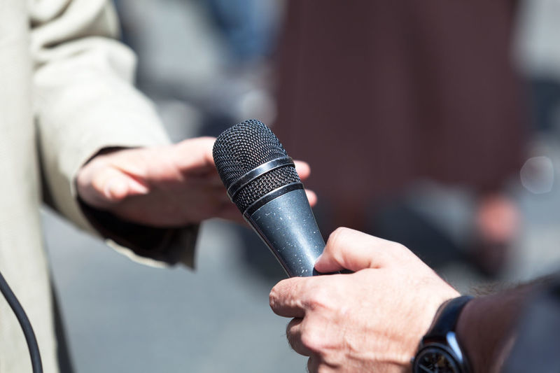 Cropped hand of male journalist interviewing businessman