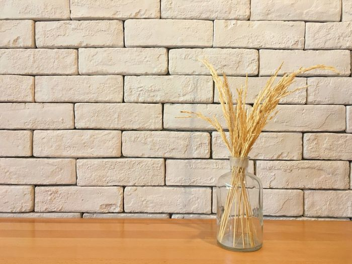 Brick Wall No People Indoors  Close-up Dry Grass Background Home Decor Dry Grass In Bottle Wood Table