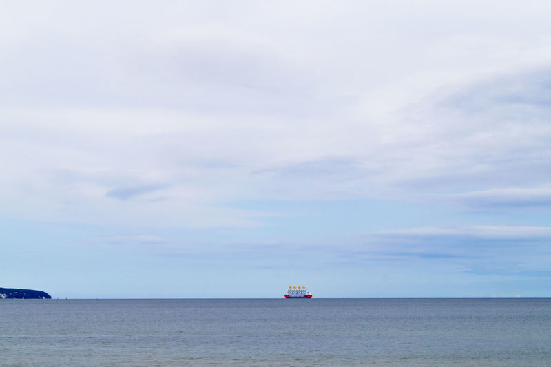 Distant view of ship against cloudy sky