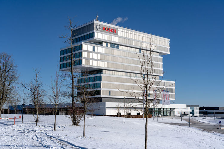 Built structure on snow covered land against blue sky