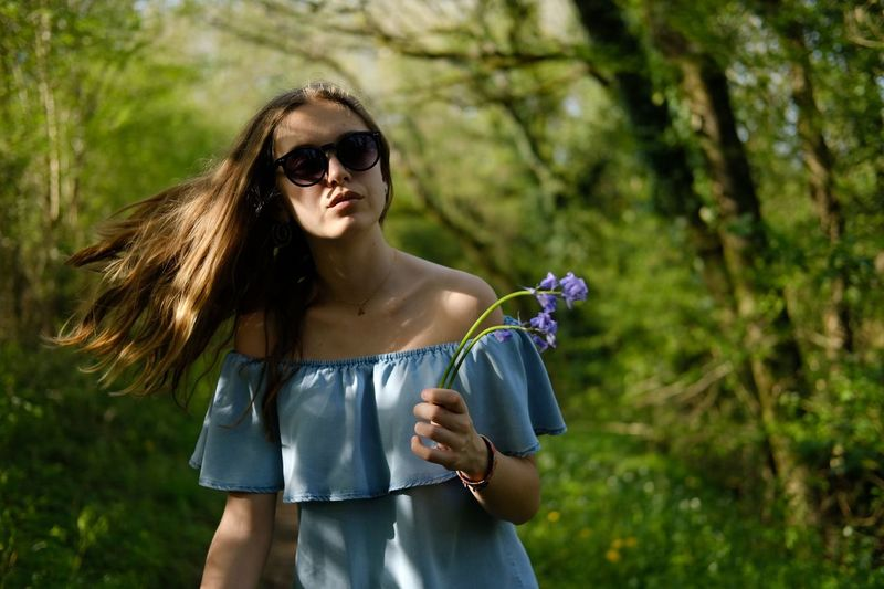 Teenage girl holding flower while tossing hair in forest