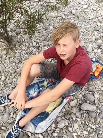 Young Boy Sitting On Rocks
