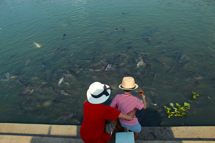 Children are feeding fish at the Tha Chin River Adult Bonding Casual Clothing Clothing Day Hat High Angle View Lake Leisure Activity Lifestyles Men Nature Outdoors People Positive Emotion Real People Rear View Sun Hat Togetherness Two People Water Women