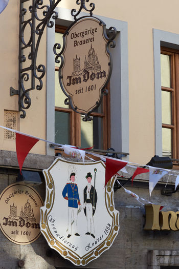 NEUSS, GERMANY - AUGUST 08, 2016: Signs indicate age of a historic building Advertising Business Finance And Industry City Life City Street Commercial Dock Culture Downtown Historic Historic Buildings Urban History Medieval Neuss, Germany Pedestrants Shopping