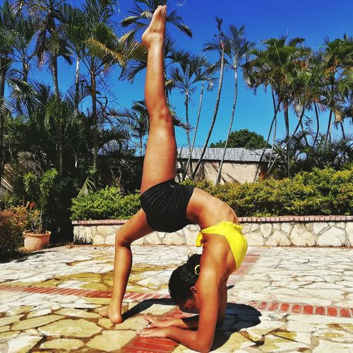 Full length of young woman practicing yoga on sunny day