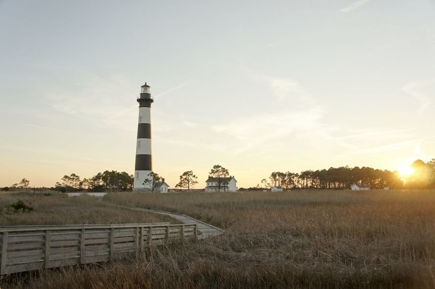 Architecture Beauty In Nature Bodie Island Lighthouse, Nc Built Structure Cloud Cloud - Sky Field Grass Grassy Hill Horizon Over Land Landscape Lighthouse Nature No People Outdoors Outer Banks, NC Rural Scene Scenics Sky Sun Sunset Tranquil Scene Tranquility