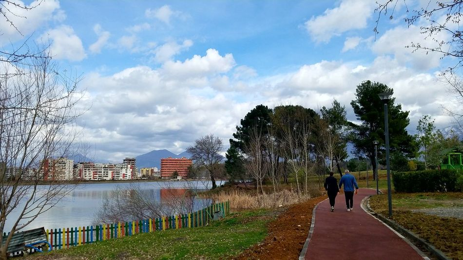 Beauty In Nature Mountain Range Mountain In The Background Clouds And Sky Artificial Lake Of Tirana Fence Photography Colorful Green Color Cityscape Streetphotography People Photography Walking Around