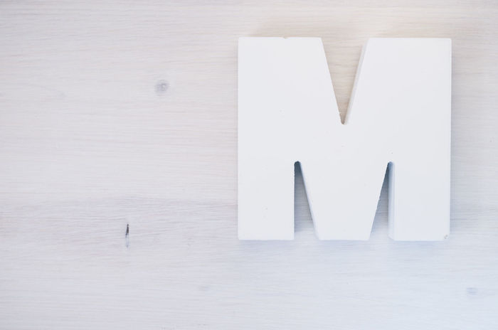 M - letters alphabet Alphabet Close-up Day Indoors  Letter Minimalism No People Object Page Paper Symbol Symbolic  Table White White Background Wood - Material Wooden Break The Mold