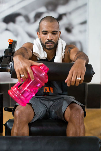 Tired Man With Water Bottle Sitting On Chair In Gym