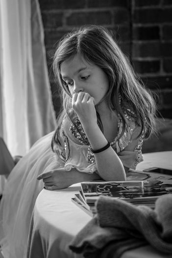Thoughtful girl standing by table at home