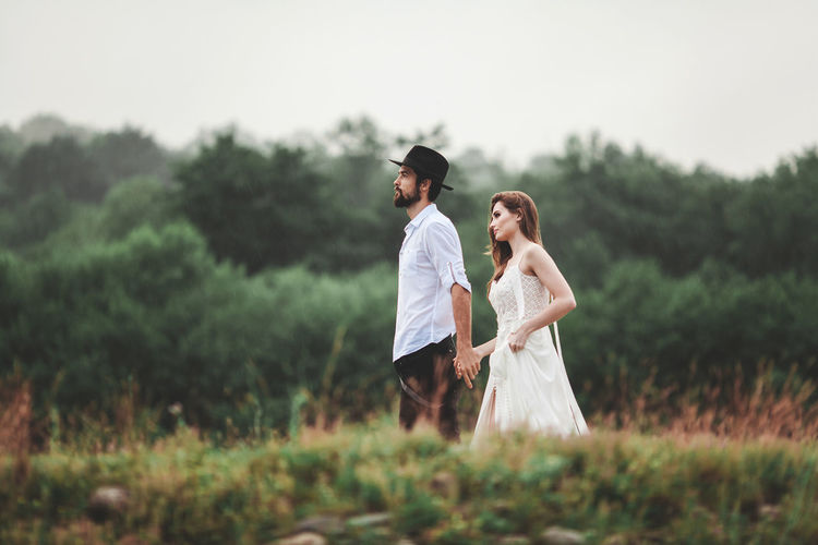 Two people. A loving couple in nature. Bride and groom. She is wearing a white wedding dress, he is wearing a black hat, shirt and trousers. The guy wears a beard. The girl has beautiful long hair. Both young and attractive, slender figures and beautiful faces. They walk in a meadow, on which a green grass grows. Warm summer day. Happy young family. Healthy relationships. Real emotions. Wedding in nature. Shooting with daylight. Fashion Adult Bonding Casual Clothing Country Life Couple - Relationship Day Field Land Leisure Activity Lifestyles Love Men Nature Outdoors Plant Positive Emotion Real People Standing Three Quarter Length Togetherness Tree Two People Women Young Adult