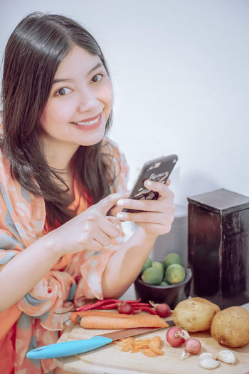 Portrait of smiling woman using phone while cutting vegetables at home