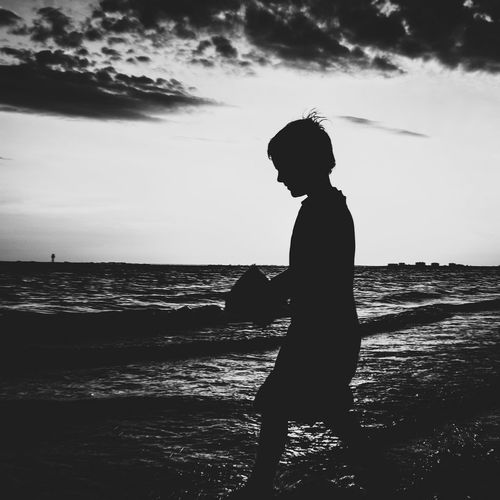 Silhouette boy standing by sea against dramatic sky