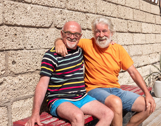 Portrait of smiling senior men sitting on bench against wall during sunny day