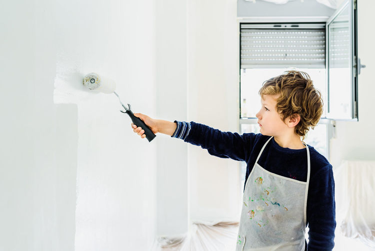 Boy standing against white wall at home