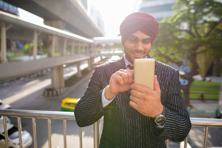 Man holding smart phone while standing outdoors