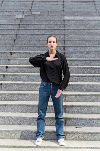 Full length portrait of a casually dressed young woman posing One Person Casual Clothing Jeans Staircase Caucasian Young Woman Young Adult Outdoors Outside Natural Lighting Steps And Staircases Looking At Camera Portrait Front View Standing Posing Serious Day Natural Light Jeans Full Length