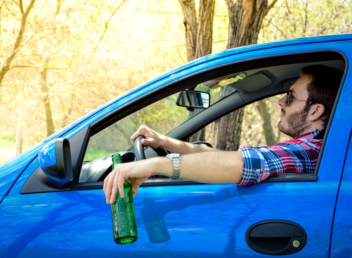 Man holding beer bottle while driving car in forest