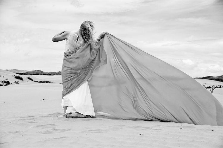 Rear view of woman with scarf standing on sand