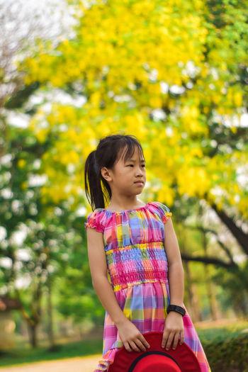 Full length of cute girl against trees