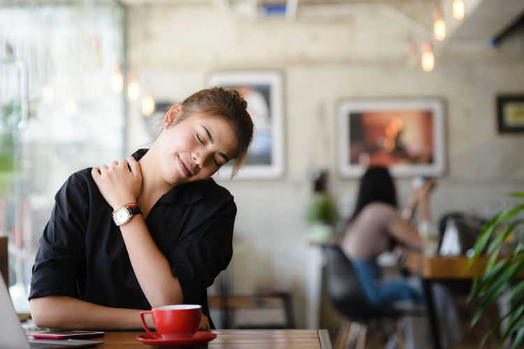 Young Woman With Neckache Having Coffee In Cafe