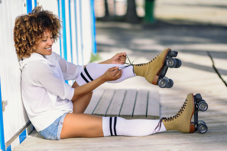 Young black woman sitting on wooden floor puts on skates. Girl with afro hairstyle wearing white sports clothes near the beach. Afro Casual Clothing Curly Curly Hair Day Full Length Happiness Holding Human Leg Leisure Activity Lifestyles One Person Outdoors People Real People Rollerblading Rollerskating Sitting Skates Smiling Young Adult Young Women