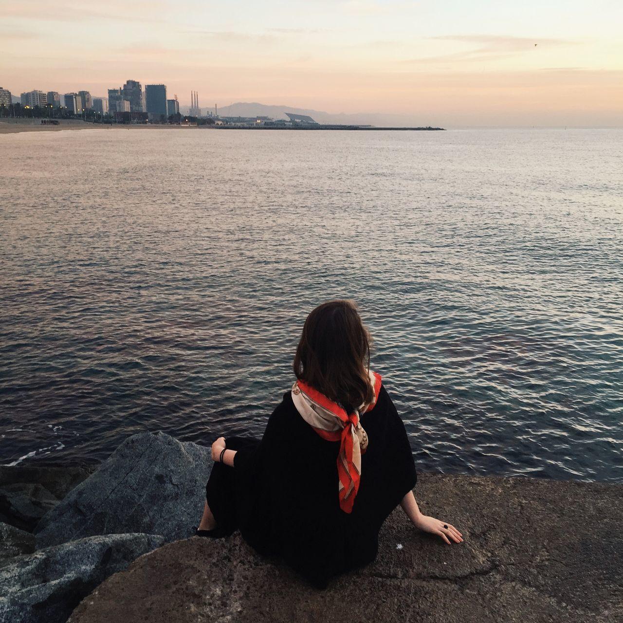 Rear view of woman enjoying sea view during sunset