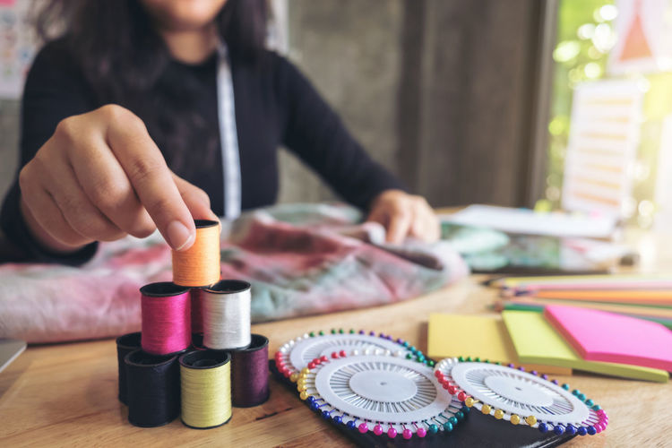 Midsection Of Fashion Designer Stacking Colorful Thread Spools On Table