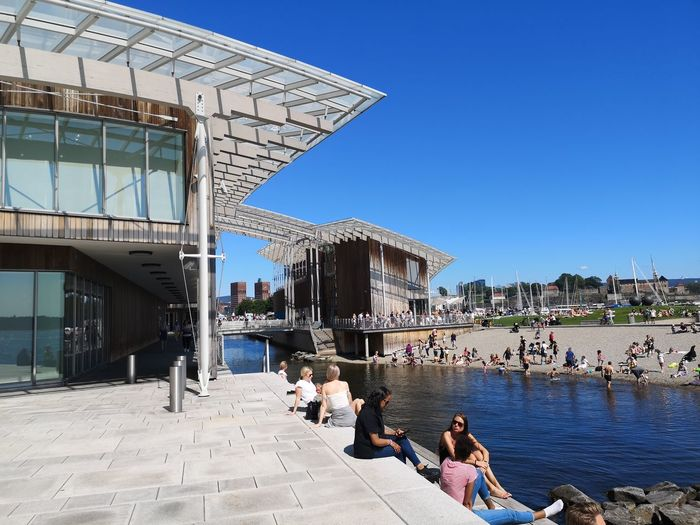 Oslo Oslofjord Norway Modern Architecture City Clear Sky Water Beach Blue Summer Women Sunlight Sand Sunny Town Square Sunbathing