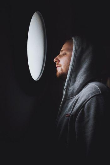 Man looking through window in darkroom