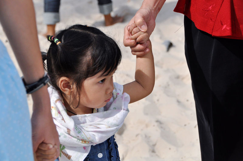 Midsection of parents holding daughter hands at beach