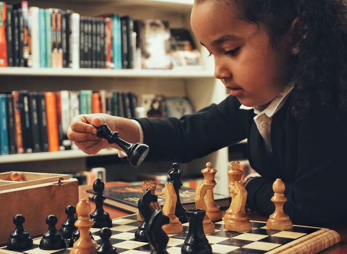 Girl playing chess by bookshelf
