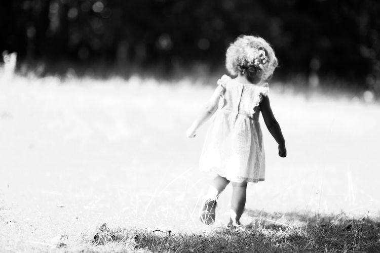 Rear view of girl walking on field