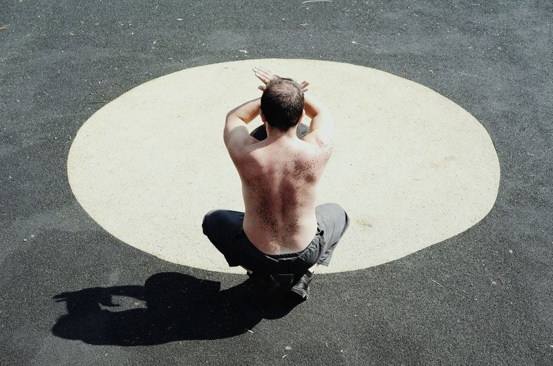 Rear view of shirtless man exercising at playground during sunny day