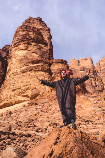 Full length of man with arms outstretched standing on rock formation